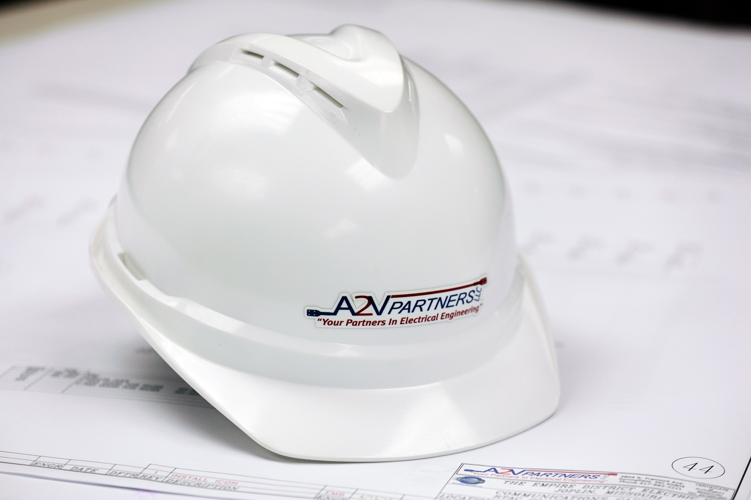 Hard hat on top of electrical engineering blueprints at the A2V Partners office in Springfield MO
